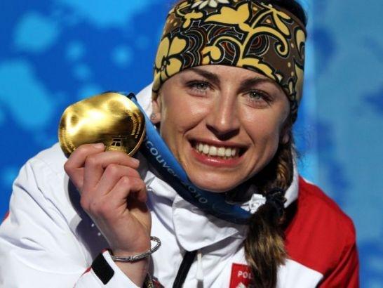 Szczęśliwa Justyna Kowalczyk z dumą prezentuje złoty medal olimpijski (fot. PAP/EPA)