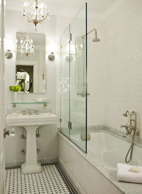 stunning, elegant bathroom design with white pedestal sink, rectangular frameless mirror, Restoration hardware vintage glass shelf, soft gray walls paint color, marble basketweave tiles floor, subway tile shower surround, rain shower head and crystal chandelier.