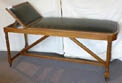 A Leather Upholstered Oak  Doctor's Examination table or bed with adjustable head rest.