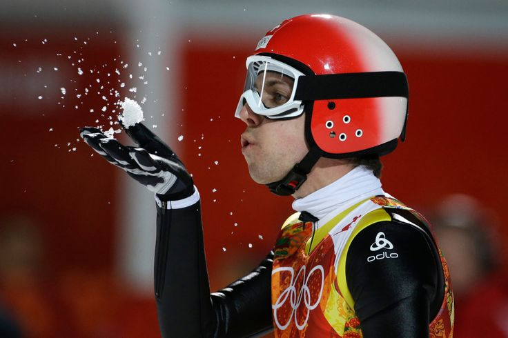 Switzerland's Simon Ammann blew snow off his hand after his second attempt during the ski jumping large hill final at the Sochi Winter Olympics. (Photo: Gregorio Borgia)