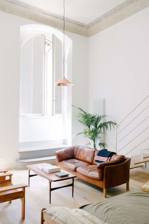 cognac leather couches, shades of moss green and rose gold, tall ceilings and lots and lots of white