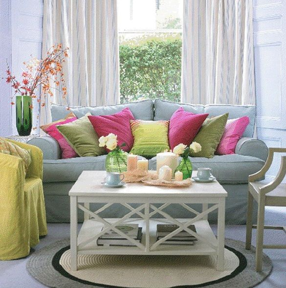 Soothing living room with grey and yellow sofas with green purple decorative cushions combined by white small square table above round rug