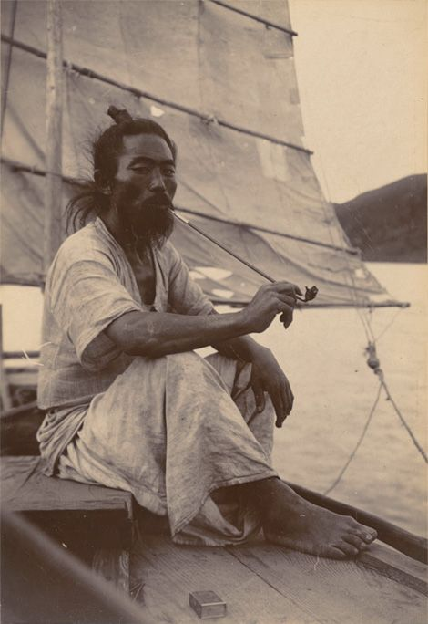 """""""Korean sailor takes a break from trasporting cargo and people, sitting under the shadow from the sail, smoking from his long bamboo pipe. He wears cool hemp clothes."""" From the Cornell University Library collection."""
