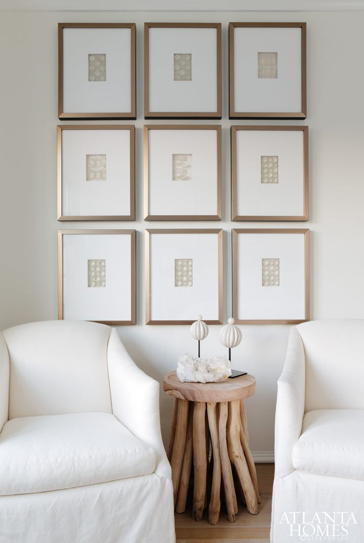 Art work hung in grid above two chair conversation area
