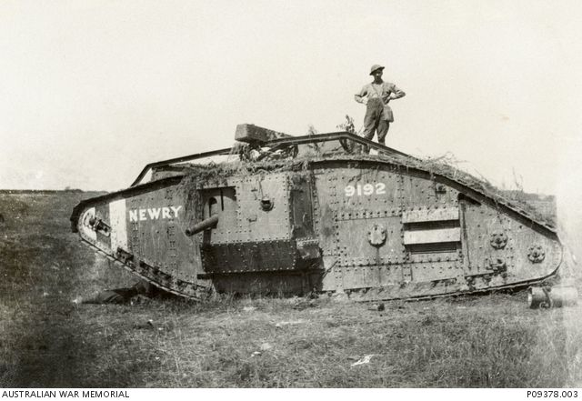 A serviceman stands on 'Newry', a Mark IV male tank No. 9192, believed to have been part of the British tank force that supported the Australian attack east of Amiens between August-September 1918.As a result of the Germans using many captured British tanks of this type, the British adopted a distinctive system of red-white-red markings on their tanks. ...