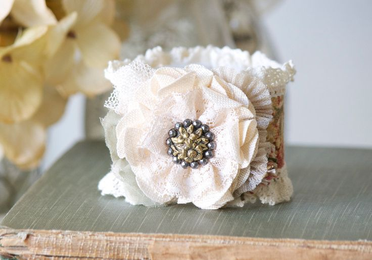 This cuff bracelet features pretty textiles, lace trim and an eye-catching vintage button with a beautiful floral design. A unique gift for women and girls who love to wear one-of-a-kind jewelry. A ve