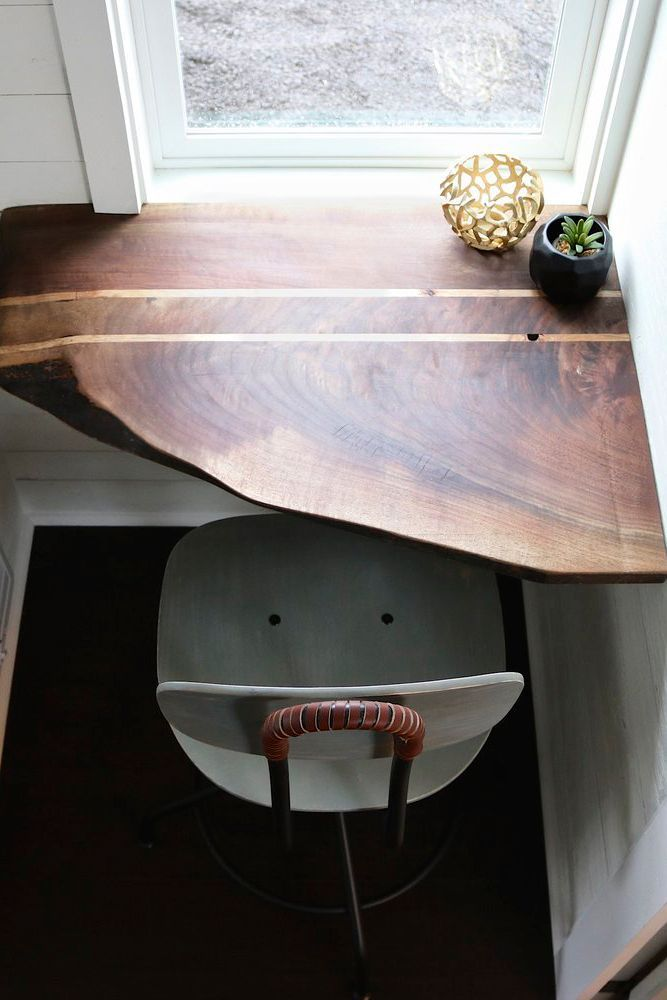 A built-in walnut corner desk with chair sits in front of a large window, providing a wonderful place to work.