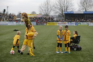 The Sutton United mascot, Jenny the Giraffe, entertains the mascots and supporters