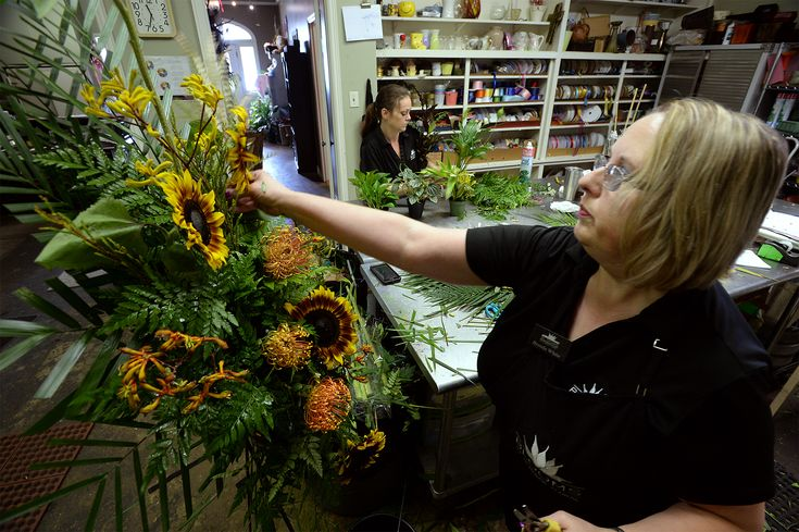Brenda White carefully examined a wire easel in the back room of her flower shop Tuesday, pinning yellow lilies, pincushion protea and large brown sunflowers into an arrangement bound for a funeral home in Orange.  Instead of funeral sprays and sympathy plants, many families are asking friends and colleagues to remember their loved ones by making donations to charities or giving their time.
