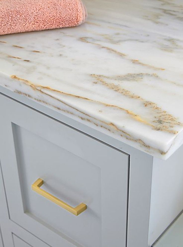 Stunning bathroom vanity painted light grey accented with brass hardware and topped with white marble with gold and bronze veining. Noras