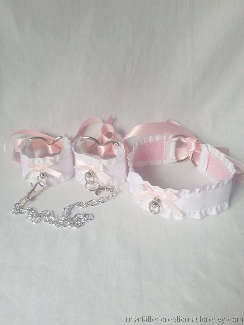 ♥ Set of two (2) wrist cuff restraints & one (1) matching collar  ♥ Soft white faux fur padding sewn onto the inside of the cuff gives a plush, comfortable feeling  ♥ Sturdy webbing sewn into both the cuffs & collar which makes it perfect for tugging or rough play   ♥ Pink ribbon is used to...