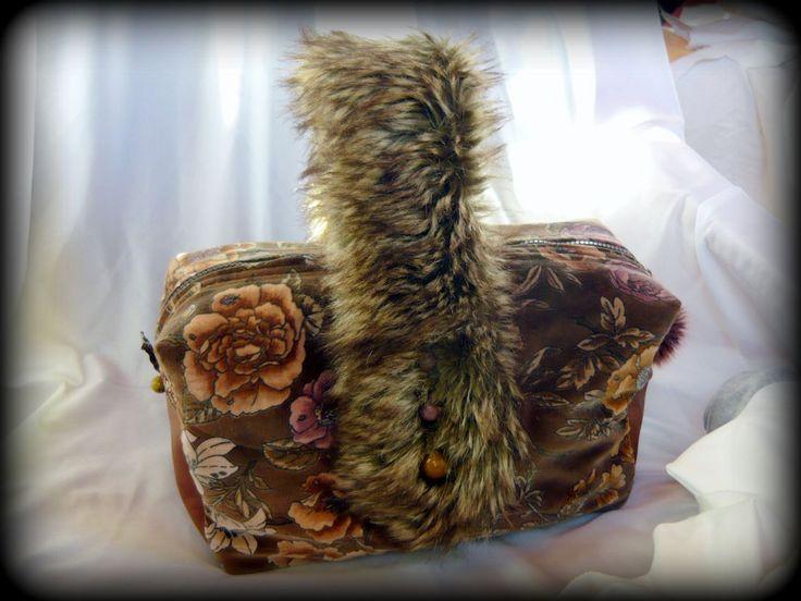 """Szőrmés-virágos bársonytáska-Handmade by Judy majoros: Virágos bársony szoknya """"átdolgozásával"""" született ez a szőrmefogantyús kézitáska. Két oldala, és az alja valódi bőrből készült. Műszőrméből készült fogantyúja keresztben helyezkedik el a táska tetején. Belseje mintás pamutvászonnal bélelt, és 3 zsebet rejt, valamint az alja egy kivehető merevítőt is kapott. A táska szivacsfóliával bélelt, ami nemcsak tartást ad a táskának, de vízállóságot is biztosít. Cipzárral záródik."""