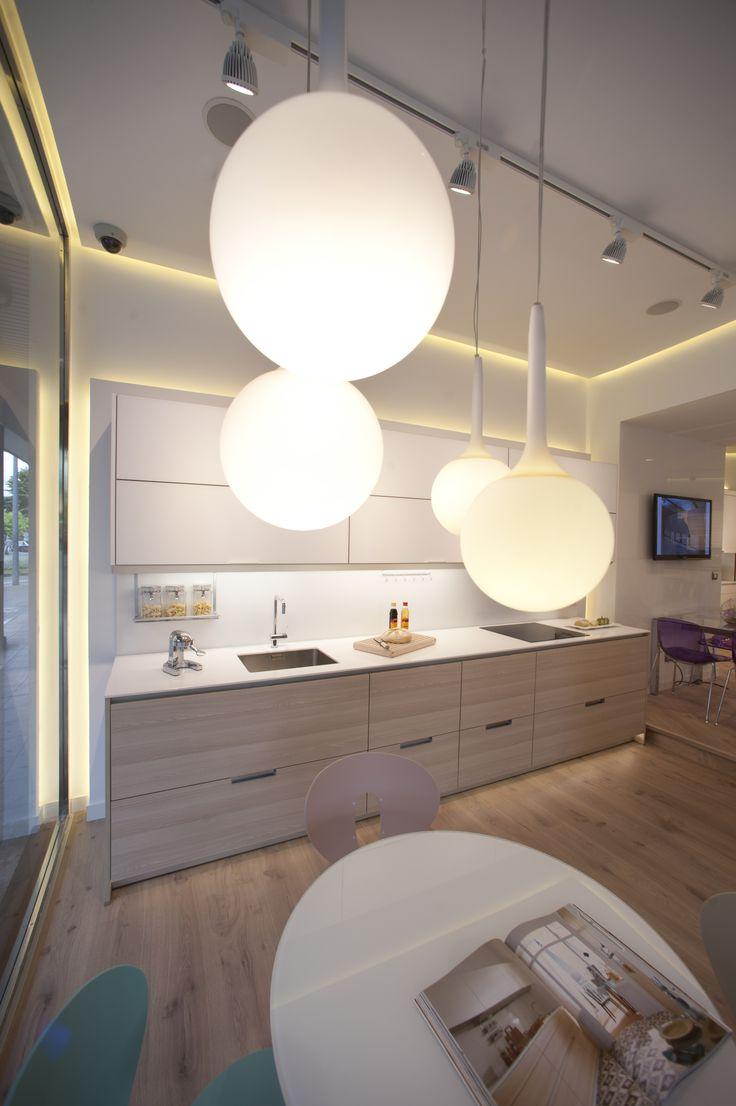Cocina en madera clara y con una iluminación que toma el protagonismo