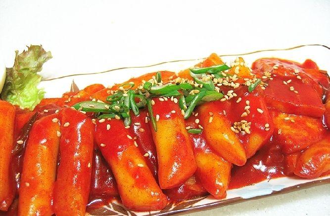 떡볶이 – Tteokbokki é um petisco coreano muito popular feito de bolo de arroz, carne, ovos, temperos, e molho picante. A versão mais comum de Tteokbokki comida atualmente é muito picante, mas no passado ele era uma fritura feita com molho de soja e bife.