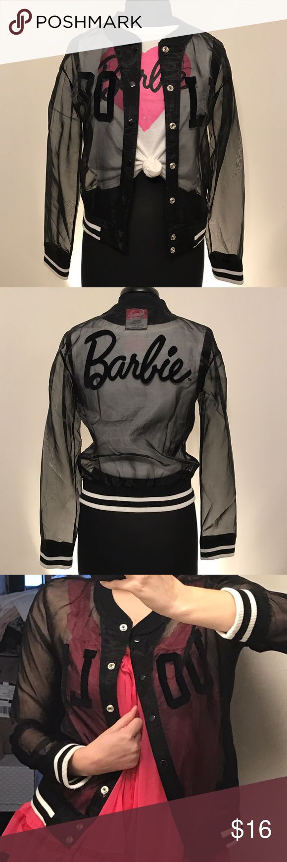 """BARBIE Sheer Black Varsity Jacket BARBIE Sheer Black Varsity Jacket with white stripes along arms and waist. The front features the word """"DOLL"""" in capital letters. On the back, BARBIE is spelled out using cursive handwritting. ©2014 Mattel Inc. Barbie Jackets & Coats"""