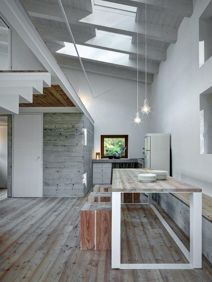Sotto il soppalco, il volume che ospita il bagno: un cubo di cemento dall'aspetto grezzo che richiama le venature del legno usato come rivestimento per pavimento e arredi.