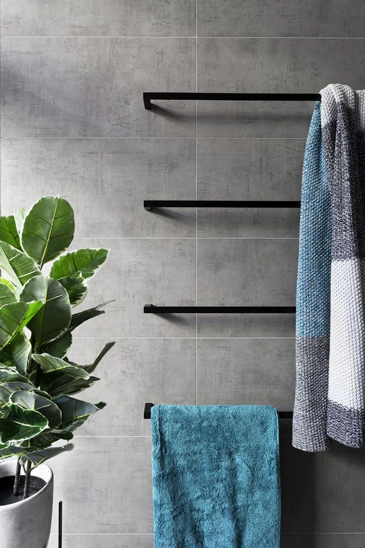 In this modern grey and white bathroom, matte black accents like towel bars add a sophistication to the bathroom, while the touches of blue in the towels and green in the plant add a pop of color to the otherwise neutral space.
