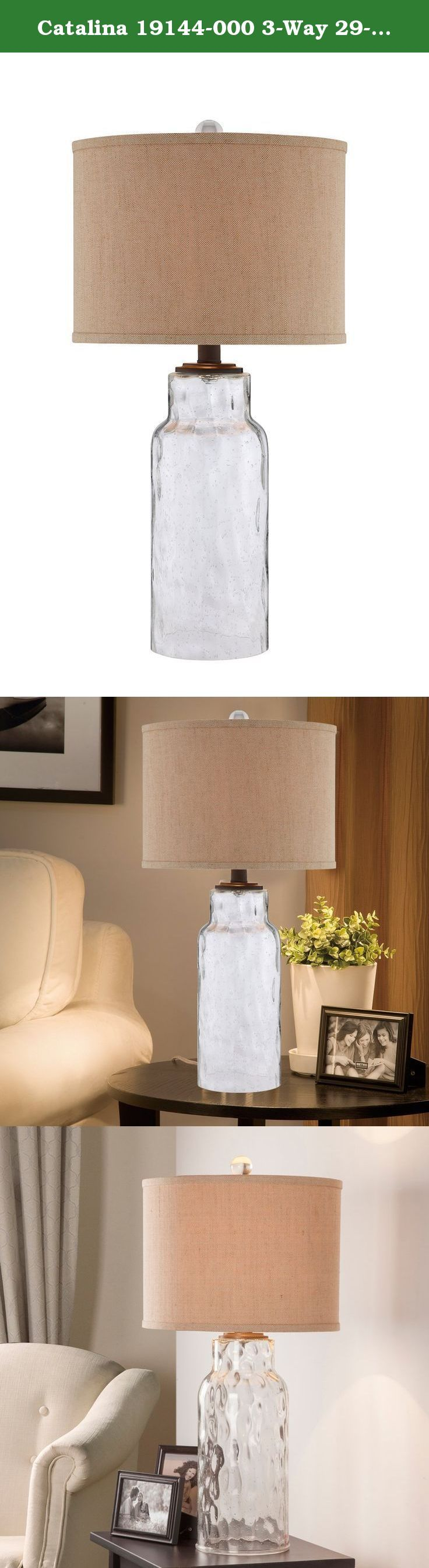 Catalina 19144-000 3-Way 29-Inch Clear Dimpled Glass Table Lamp with Textured Linen Drum Hardback Shade. The Catalina 19144-000 3-Way Table Lamp offers a stylish transitional design. The dimpled glass table lamp features a clear seeded base with metal accents in a dark bronze finish and textured linen drum hardback shade. This lamp is rated for 120-volts and uses a 3-way 150-watt incandescent bulb or 3-way E26 CFL spiral bulb. Bulb not included. The light source is soft and the…