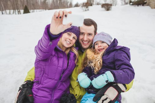 Mother and Father with daughter taking family portrait with mobile phone