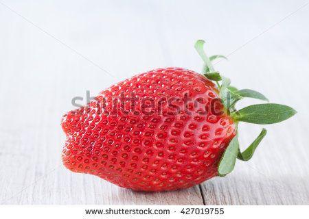 Fresh strawberry over light background. Closeup shot.