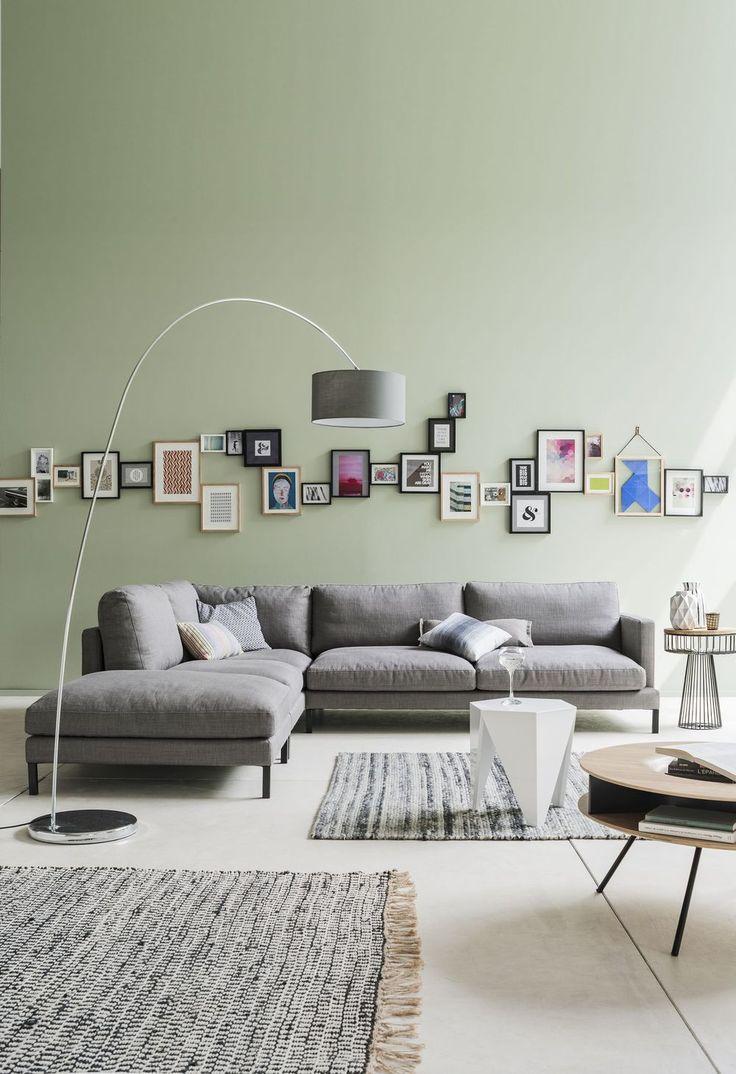 Un canapé d'angle gris zinc aux coussins moelleux dans un salon cosy aux couleurs douces avec accumulation de cadres sur le pan de mur