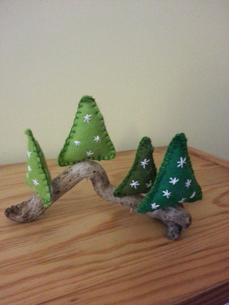 Armonici alberi di Natale arroccati sul crinale del rametto di legno.