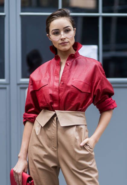 Olivia Culpo wearing red Tods button shirt beige pants glasses and boots Tods seen in the streets of Manhattan outside Zadig Voltaire during New York...