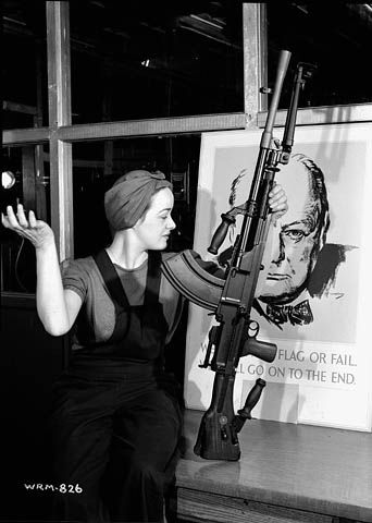 """Caption: Veronica (Ronnie) Foster, employee of the John Inglis Co. and known as """"The Bren Gun Girl"""", poses with a finished Bren gun in front of a poster of Winston Churchill at the John Inglis Co. Bren gun plant."""