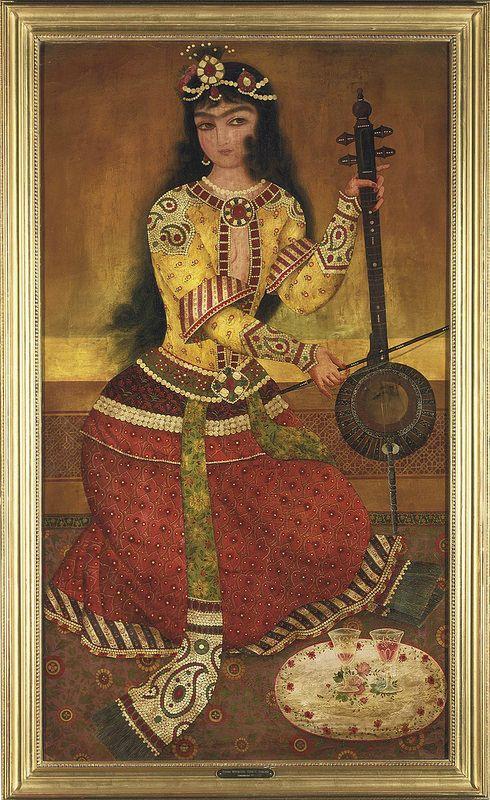 بانوی جوان در حال نواختن کمانچه ، شیوه ابوالقاسم، ربع اول قرن 19 میلادی. A COURT MUSICIAN PLAYING THE KEMANCHE  SCHOOL OF ABU'L QASIM, IRAN, FIRST QUARTER 19TH CENTURY  Oil on canvas, a young musician wearing a red floral embroidered skirt and jewelled yellow jacket kneels on a floral carpet playing a kemanche, before her a white floral tray with two glasses, very small areas of repainting, unlined, in gilt-wood frame with identification inscription below 140.8 x 80.4cm