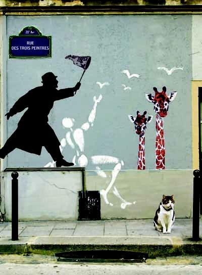 cat sitting under Nemo street art in Paris