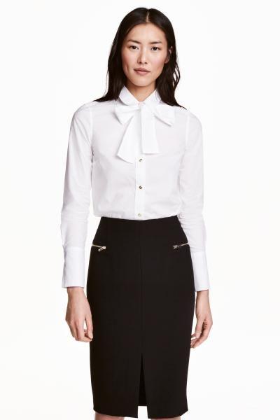 Katoenen hemd met striklint: Een hemd van geweven katoen met een afneembaar striklint bij de hals. Het model is onderaan afgerond en heeft een stolpplooi achteraan en brede manchetten met knopen.
