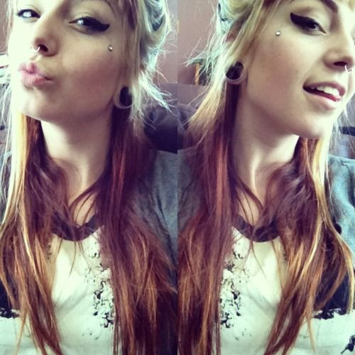Facial dermal, septum piercing and stretched lobes.