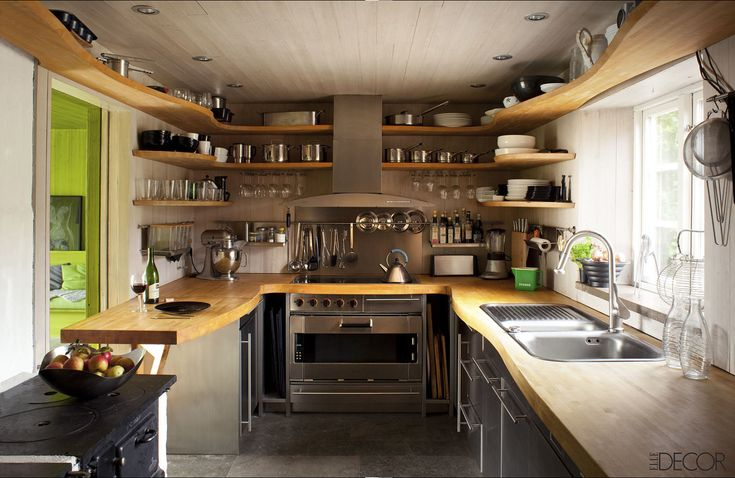 Designed by Gert Wingardh, this Swedish kitchen's custom countertops and shelving are birch, the oven and cooktop are by Gaggenau, and the antique stove in the foreground is original to the house. Tour the entire home.   - ELLEDecor.com