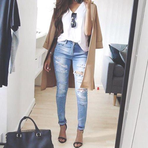 Casual stijl. Ripped jeans met witte top en suède vest.