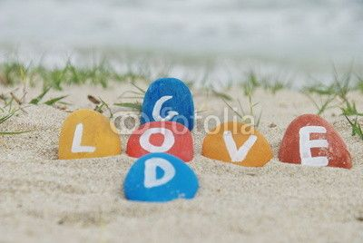 God is love and love is God. Colourful stones composition on the beach