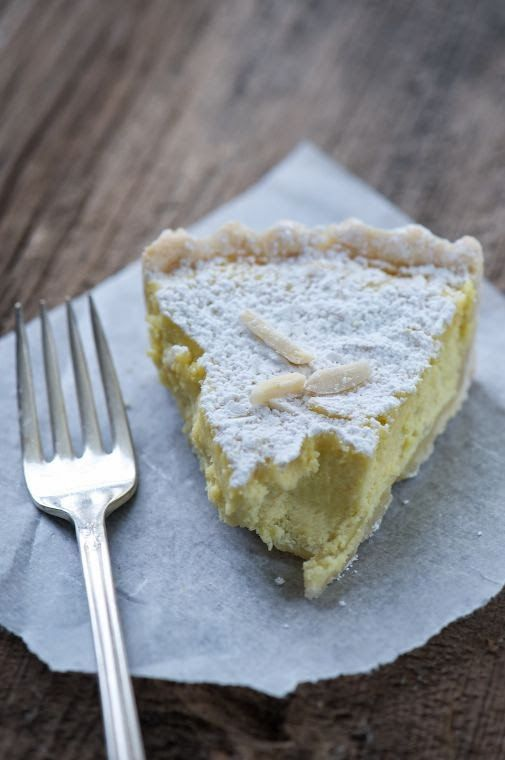 Grandmother's cake ( Torta della Nonna) with custard and pine nuts recipe. The grandmother's cake is a sweet delicate flavor of an ancient and amazing goodness.  Easy to prepare because it is made with few ingredients, the grandmother's cake with cream and pine nuts is a sweet delicate, a surprising goodness. It is a sweet typical Ligurian very common in Tuscany, composed by an envelope of pastry covered with pine nuts and powdered sugar that hides inside a savory custard filling