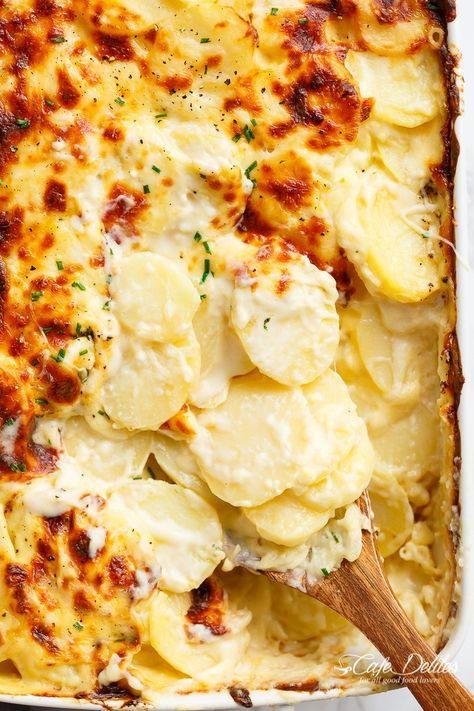 Garlic Parmesan Scalloped Potatoes layered in a creamy garlic sauce with parmesan and mozzarella is the best side dish to any meal! | http://cafedelites.com