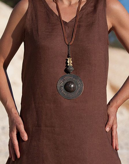 Hand hammered and patinated brass disc pendant with clay bead ( Mali) and Baule bead on leather cords. Almathe Collection