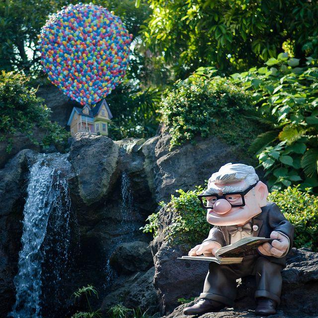 "Carl Fredricksen reads from his ""New Adventure Book"" in a beautiful little statue garden in Tokyo Disneyland. *hugs Mickey doll and cries*"