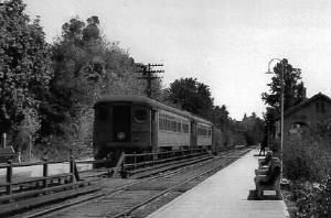 """Northwestern Pacific electric train, on the superb system serving southern Marin County, stops at Ross Station on its southbound run to the ferry terminal at Sausalito. This is 1938 and the system had less than three years more to operate. The steel electric cars got their power from a """"third rail"""" beside the tracks (under the board covers on both sides of the fence)."""