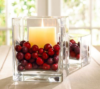 A vase filled with cranberries and a crisp white candle. From Simplified Bee.