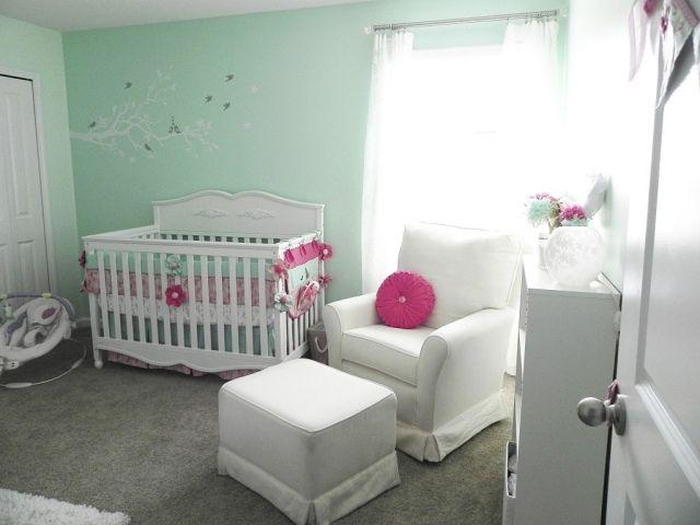 un mobilier blanc et élégant et murs en vert d'eau dans la chambre de bébé fille