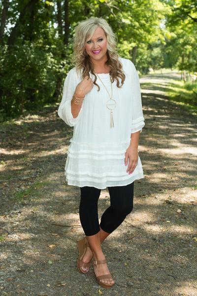 White tunic/dress w/black capri leggings, tan wedges.