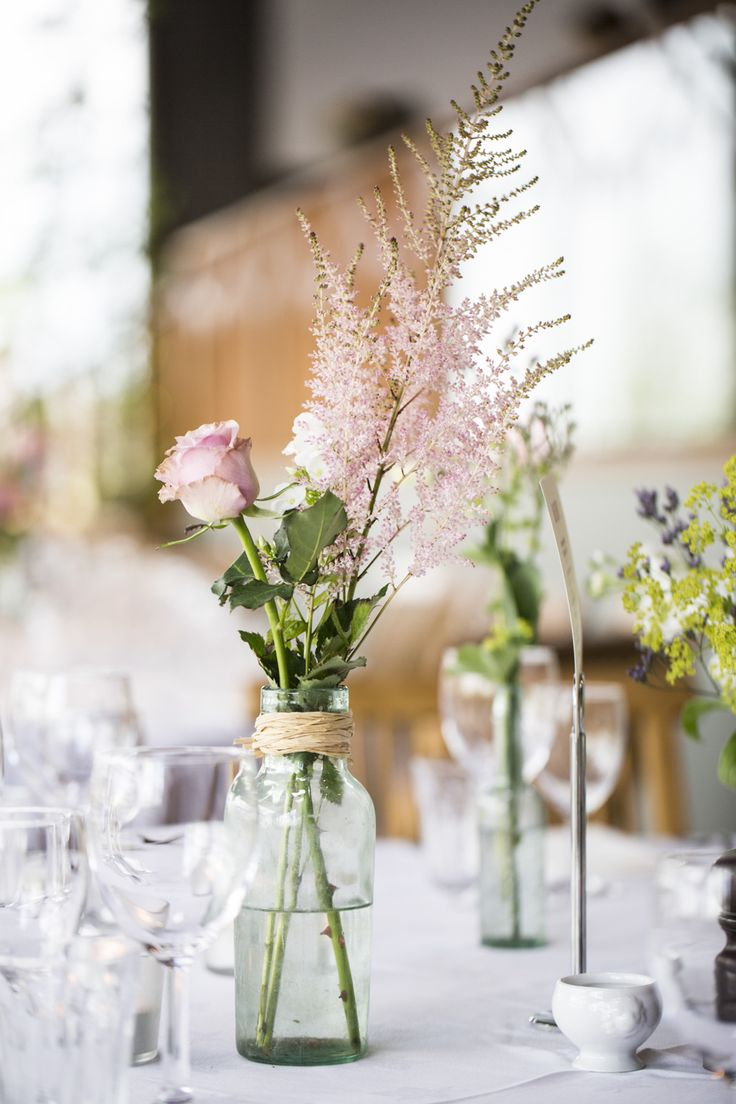 Green Bottles filled with pink flower stems | Classic Wedding | Cripps Stone Barn in the Cotswolds | Navy & Pink Colour Scheme | Images by Eleanor Jane Photography | http://www.rockmywedding.co.uk/emma-jake/