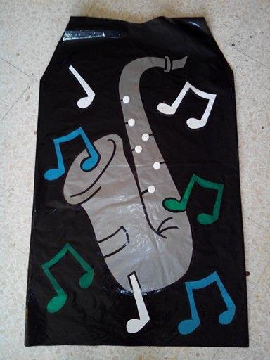 Disfraz de saxofon. Materiales: sacos plasticos para disfraces, moldes en cartulina, topitos de fieltro para los botones del saxo y pegamento.