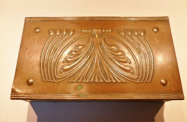 Prachtige , stijlzuivere doos in koper met vegetaal  bloemen zweepslag -motief over het oppervlak van het deksel  Binnen is de doos in houten vakken verdeeld met zwarte bekleding.  In zeer goede staat  In de bodem een merkteken : een ecusson met een X , bovenaan 2 schildpadden , beneden de Kapitalen C E D  Afm : L : 23 cm           B : 13 cm           H :6 cm