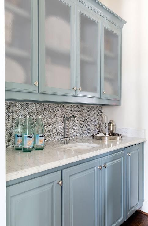 Blue bar features frosted glass upper cabinets and blue lower cabinets paired with white marble countertops fitted with a curved sink and vintage faucet as well as blue and gray marble chevron backsplash.