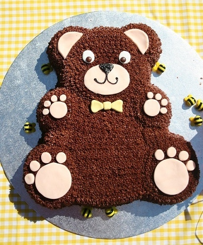 A super idea for a cake for any kids teddy bear picnic party, a teddy bear mould is usd then brown butter icing is piped all over the bear with pale pink fondant icing rolled and and cut to create the bears paws.