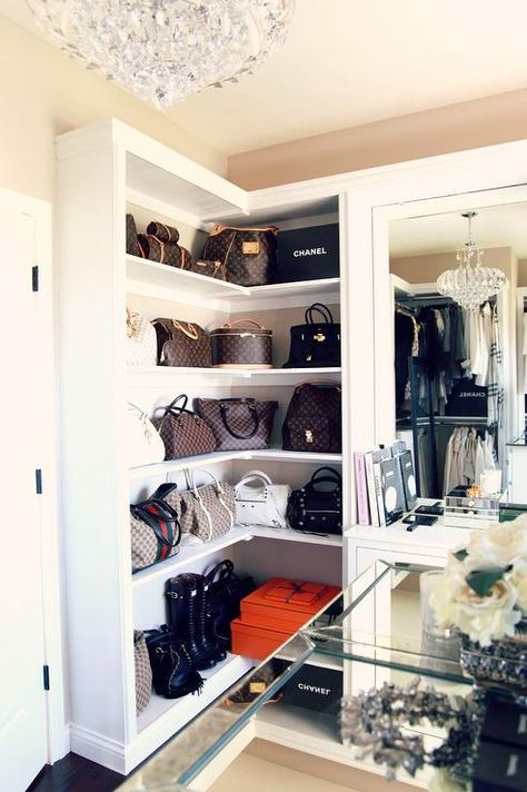 Designer bags sit against a beige wall atop built in white wrap around shelves positioned beside a dresser vanity accented with a mirror illuminated by a crystal chandelier.