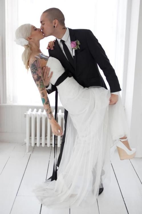 tattooed couple, cute pose. And shoes. Nice radiator. White germ-free zone. No sign of furniture. Or bed. Have they sent out for food?